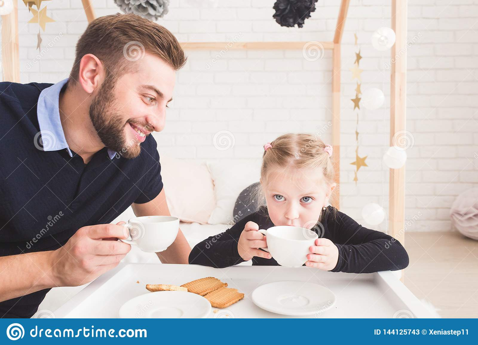 Cute little girl and her father drink tea with cookies at home.