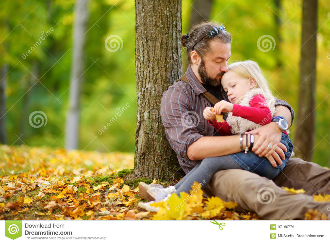 Cute little girl and her father having fun on beautiful autumn day. Happy child playing in autumn park. Kid gathering yellow fall