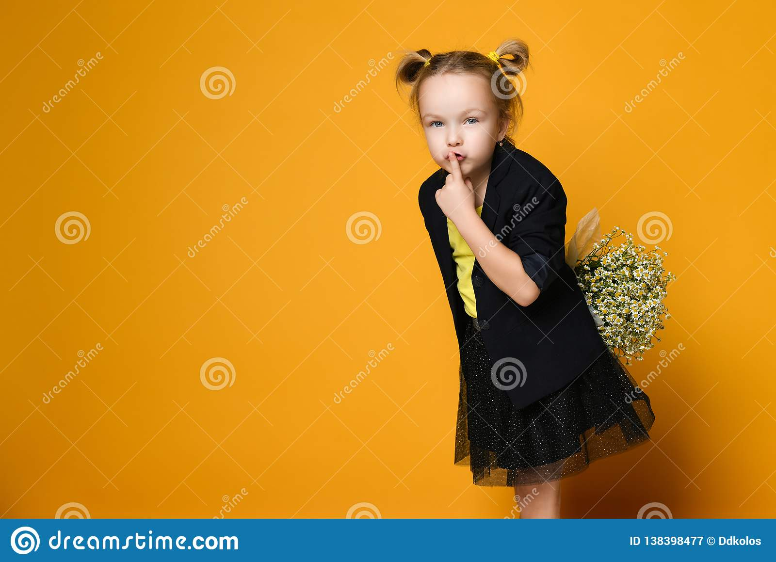 Cute little girl with her finger over mouth saying