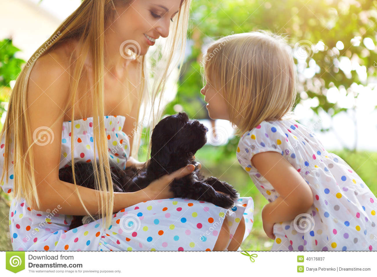 Cute little girl and her mother hugging dog puppies friendship and
