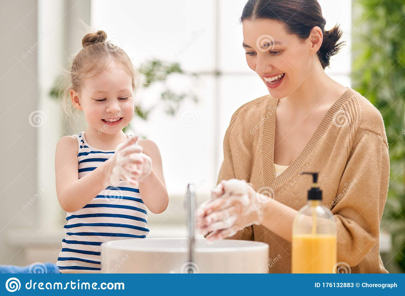 Little Girl And Her Parents Brushing Teeth Together Near