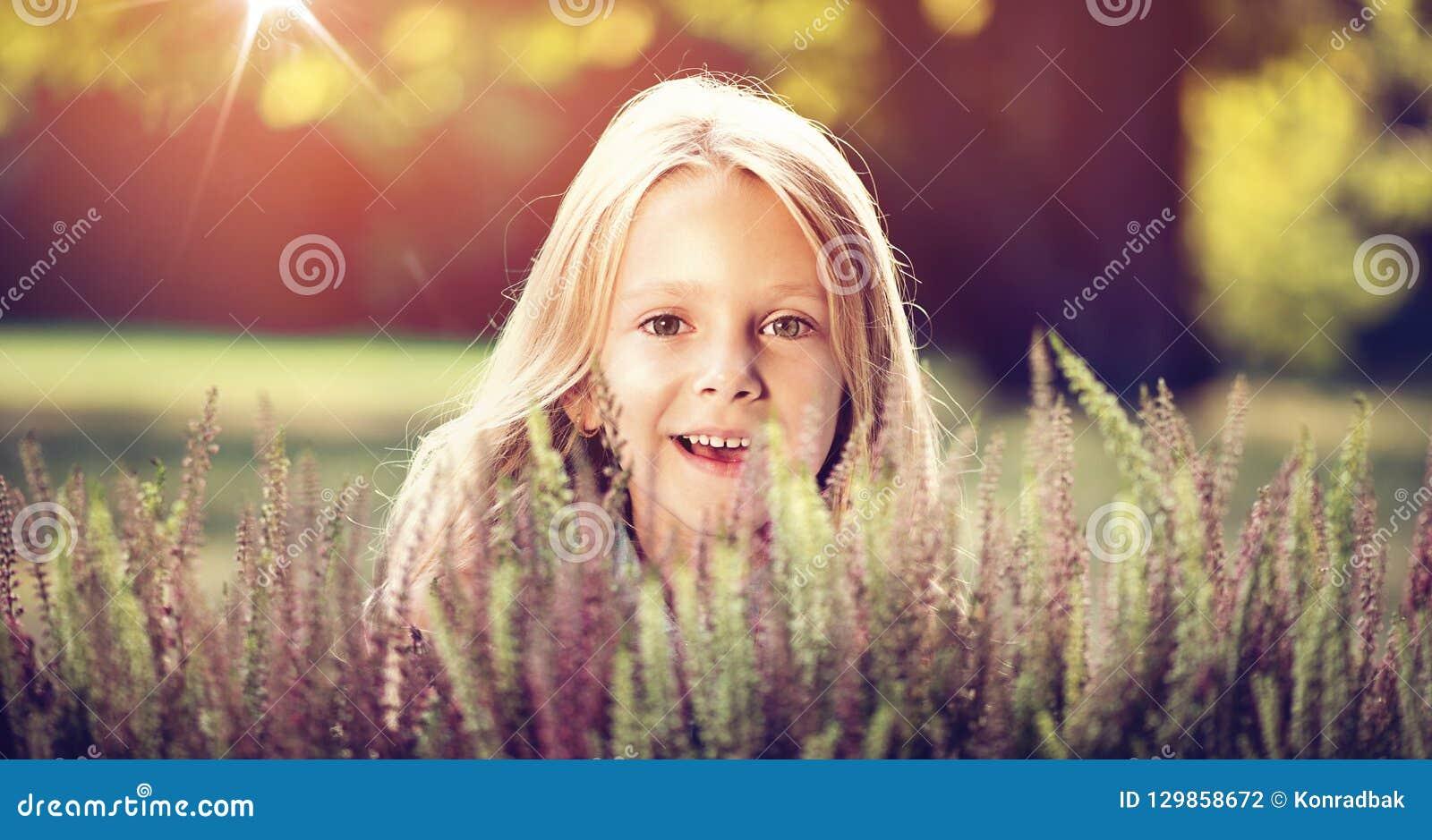 Cute little girl hiding behind heather flowers