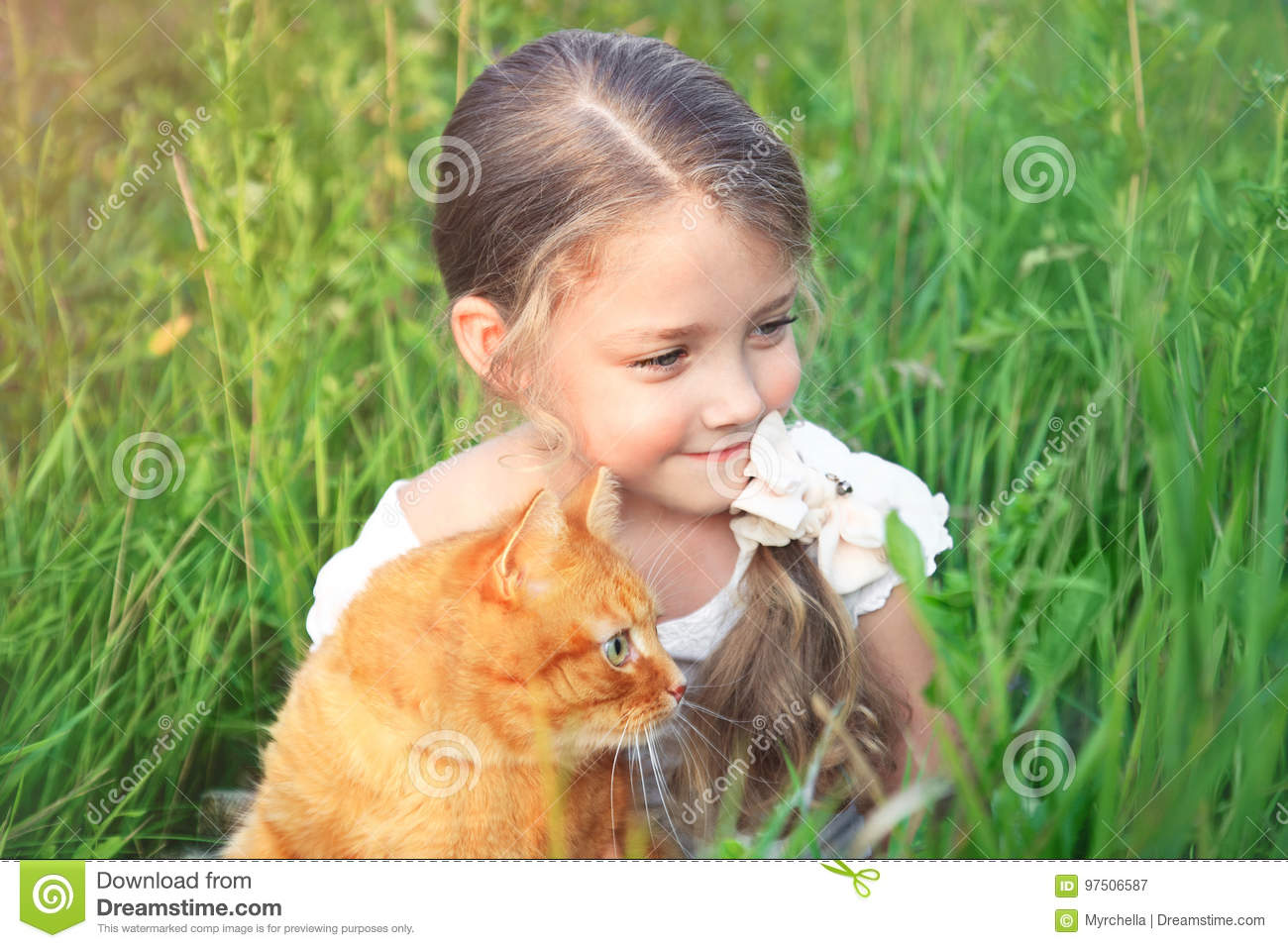 Cute little girl is holding a red cat sitting in the grass.