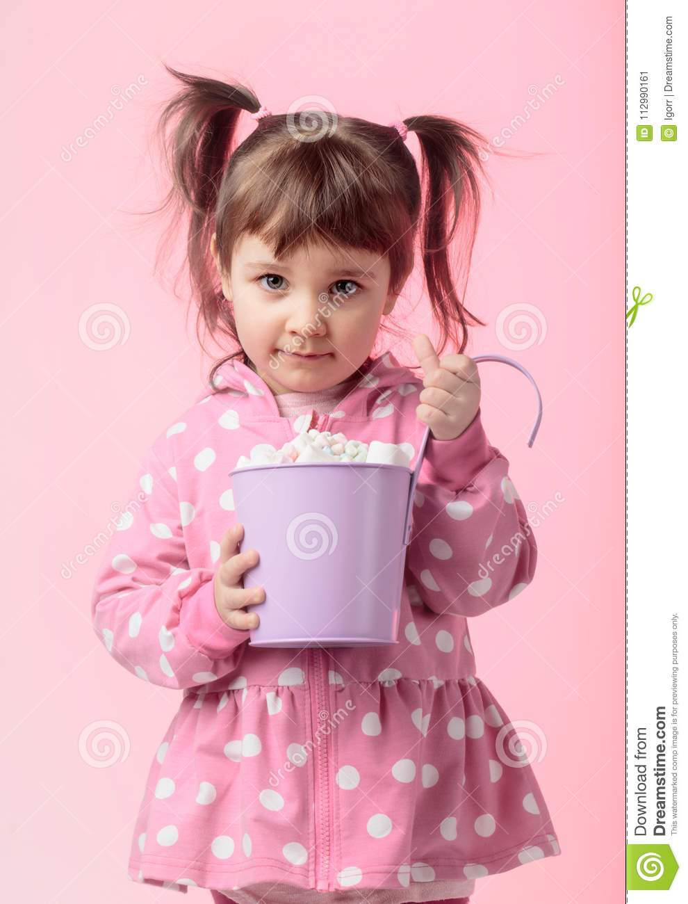 Cute little girl holding small violet bucket of marshmallow.
