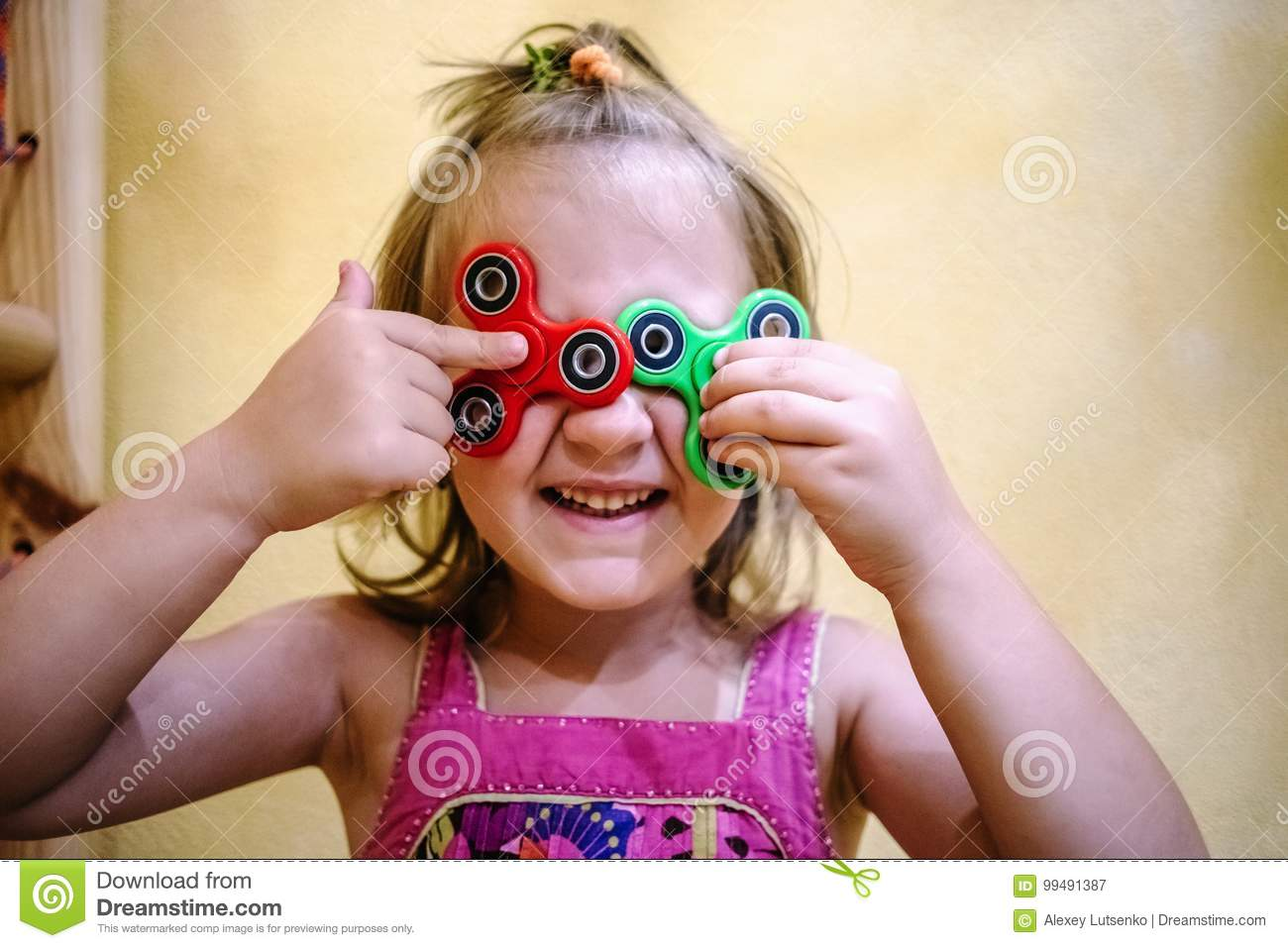 Little girl holds two fidget spinners on her face