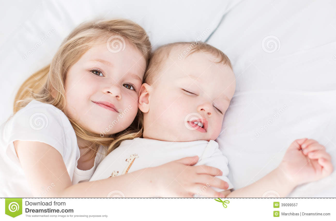 Cute Little Girl Hugs A Sleeping Baby Brother Stock Photo - Image ...