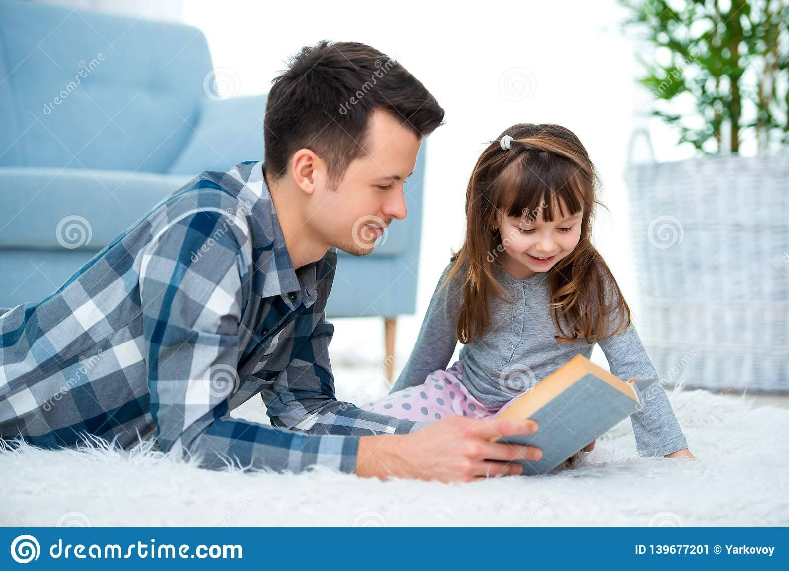 Cute little girl listening to dad reading fairy tale lying on warm floor together, caring father holding book , family hobbies