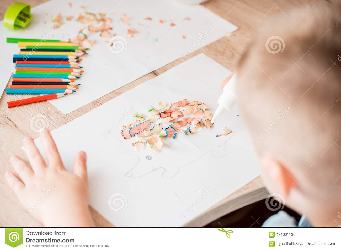 Cute little girl make applique glues colorful house, applying color paper using glue while doing arts and crafts in preschool or h