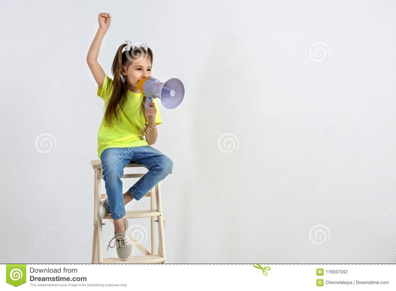 Cute little girl with megaphone sitting