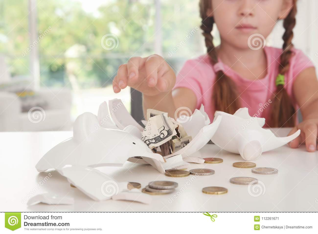 Cute little girl near broken piggy bank