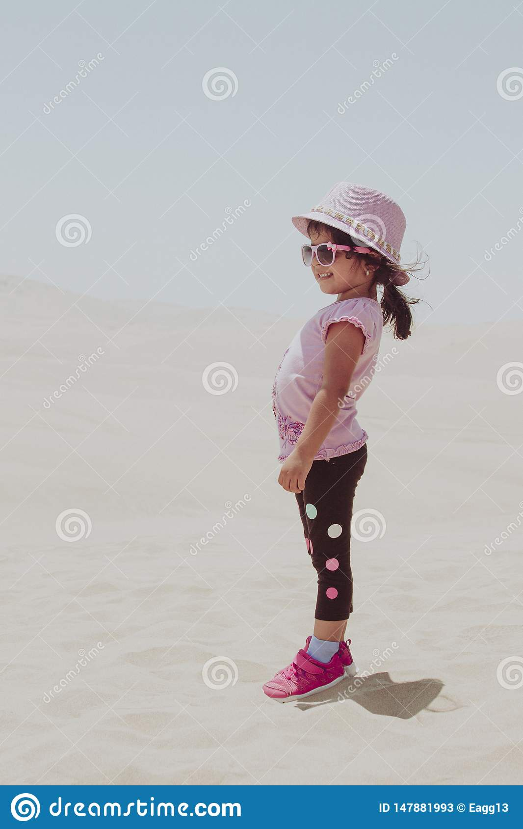 Cute little girl playing in the dunes