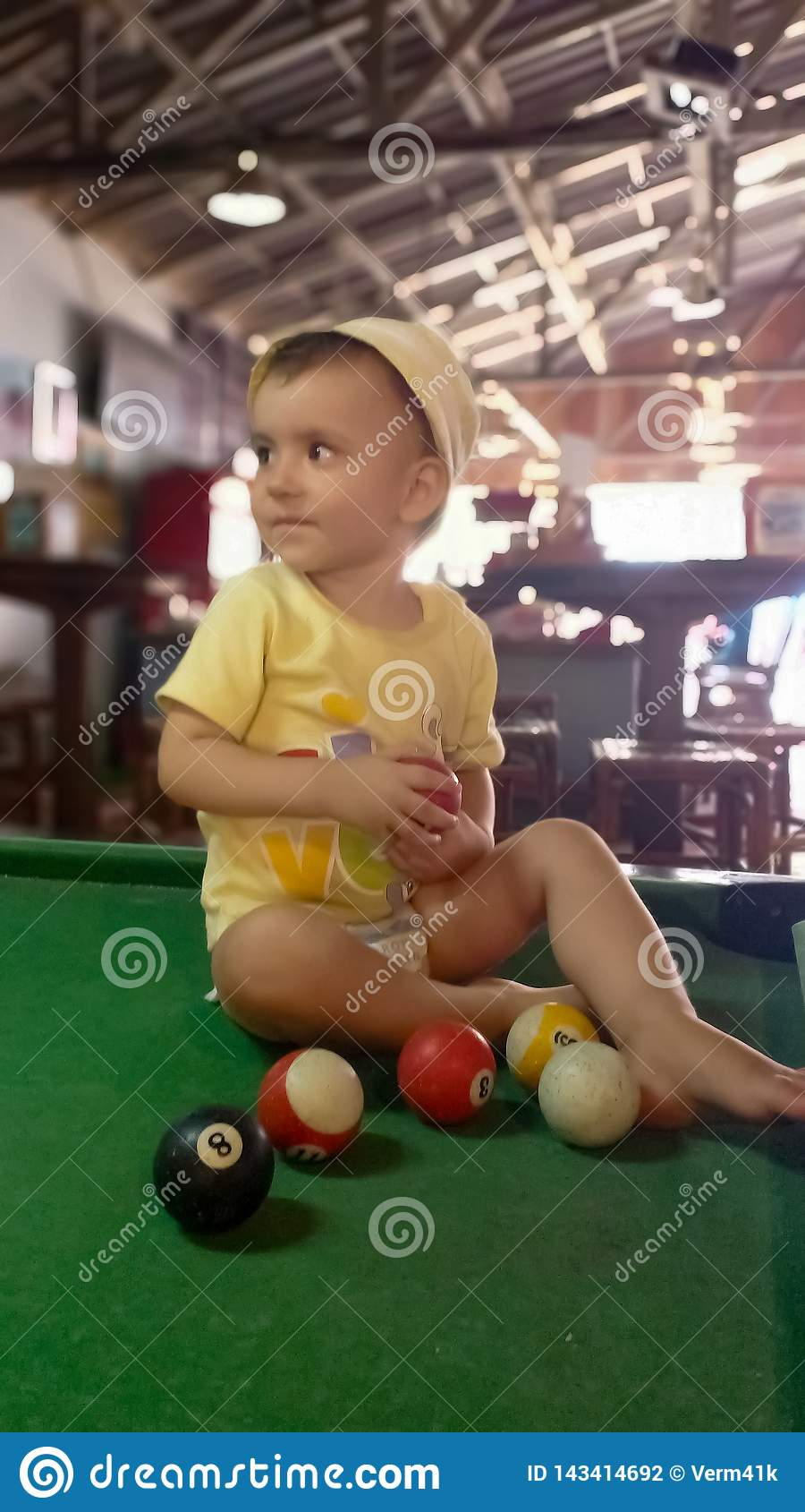 Cute little girl playing in pool table with balls.