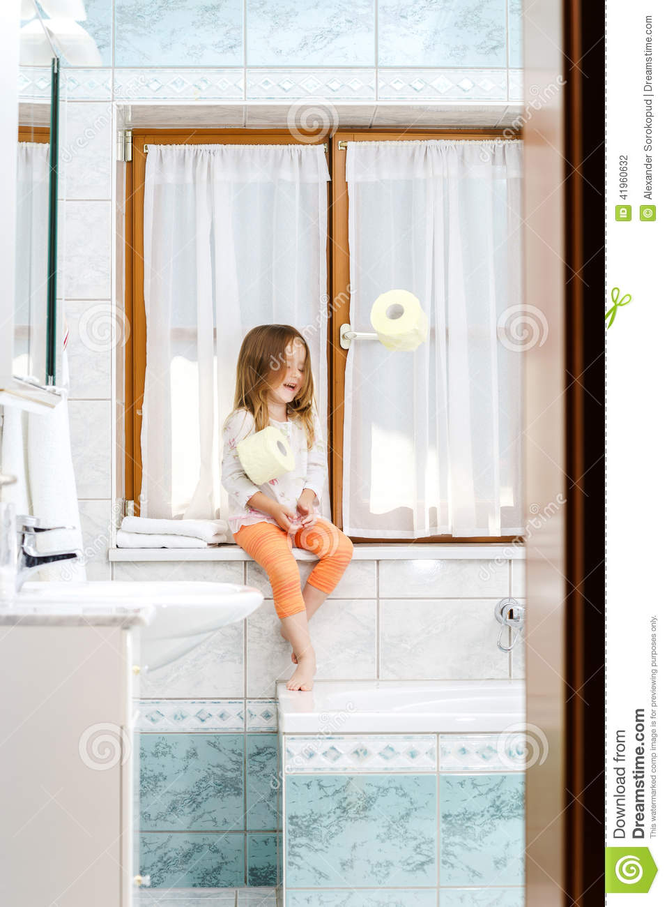 Cute Little Girl Playing With Toilet Paper Roll In A Bathroom