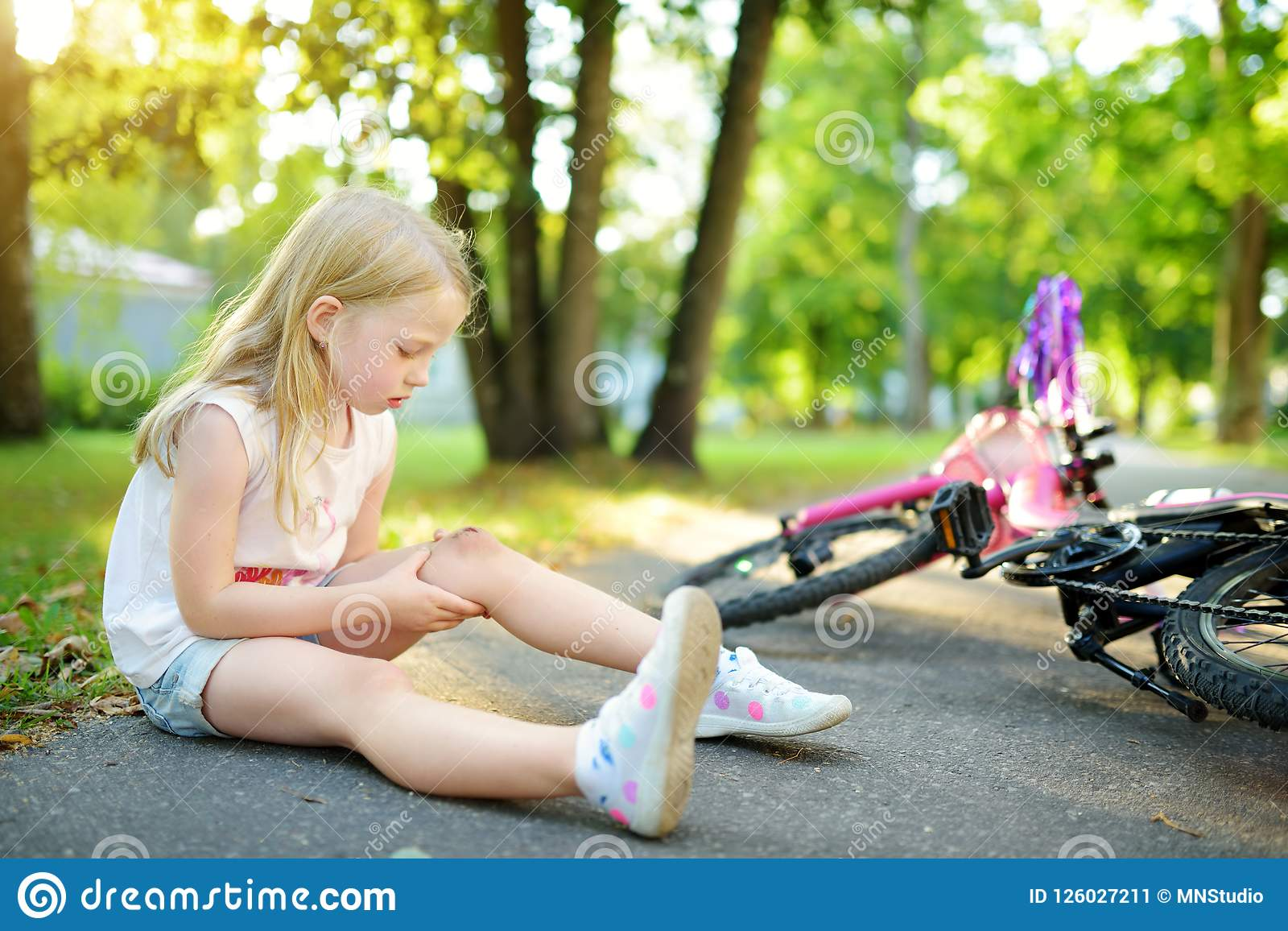 Cute little girl sitting on the ground after falling off her bike at summer park. Child getting hurt while riding a bicycle.