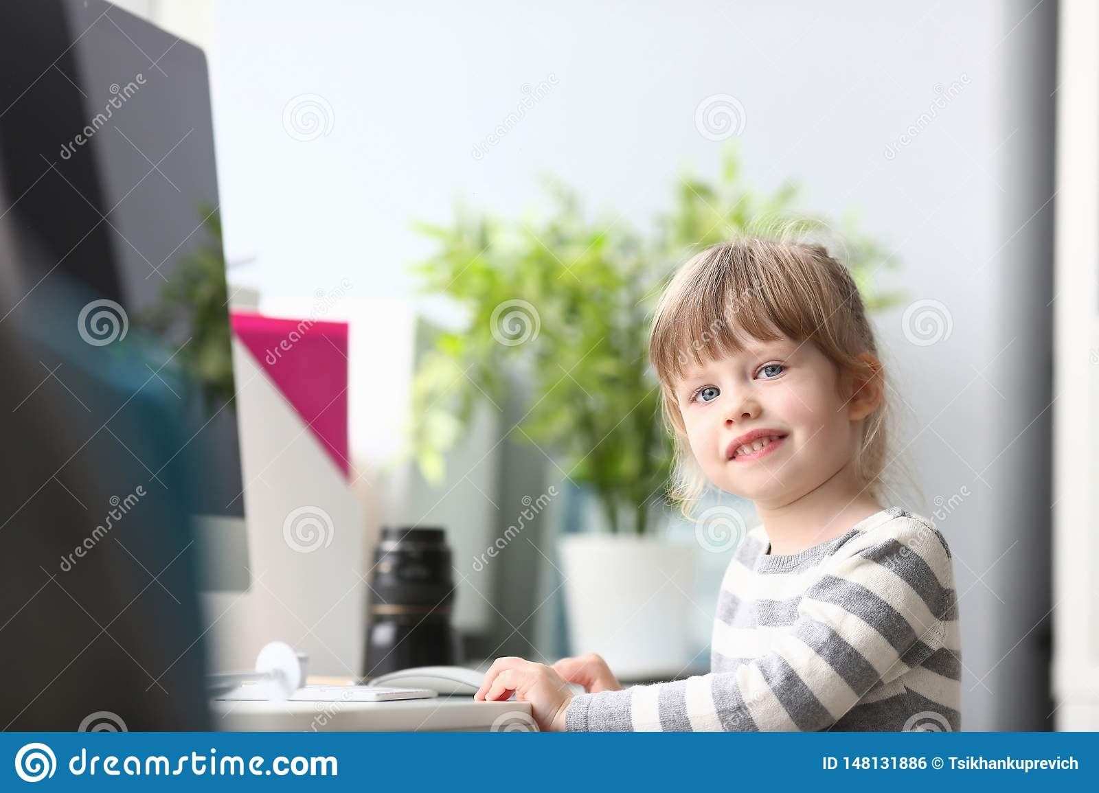 Cute little girl sitting at home at worktable looking in camera