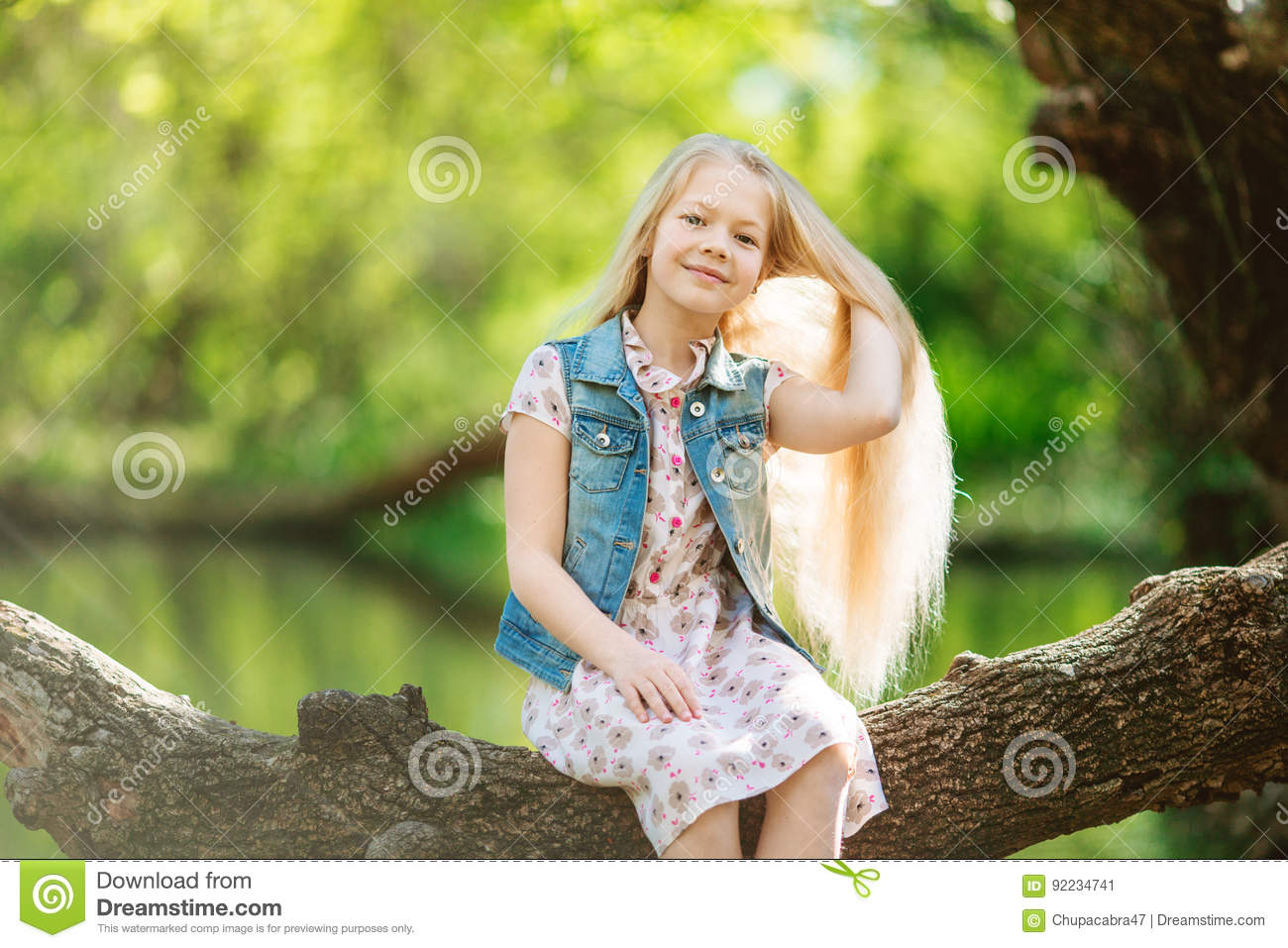 Cute Thai girl is sitting alone under the tree, near the river b ...