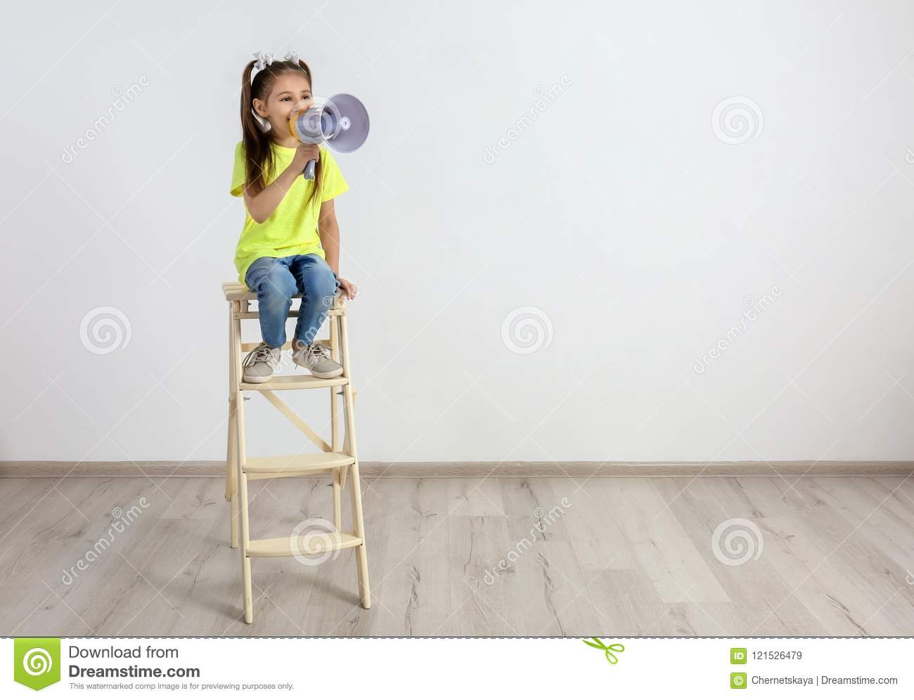 Cute little girl sitting with megaphone