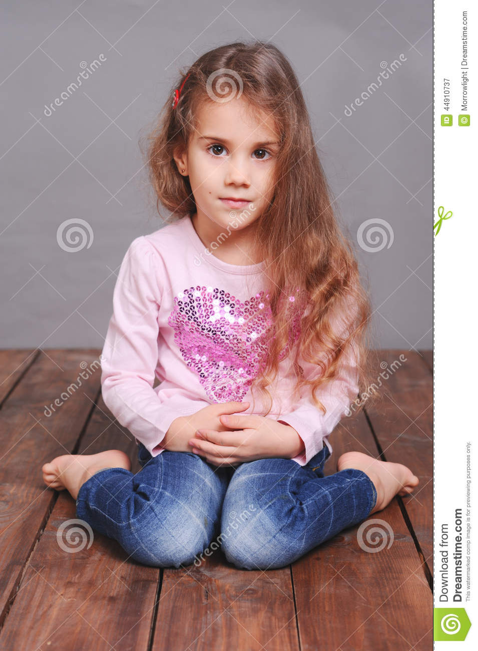 Cute Little Girl Sitting On Wooden Floor Stock Image