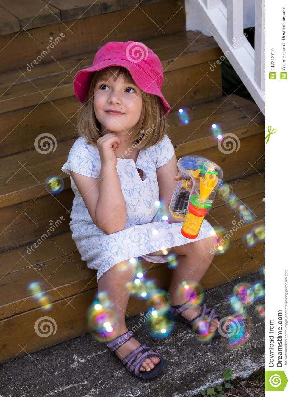 Cute little girl in summer dress sitting in stairs with soap bubbles