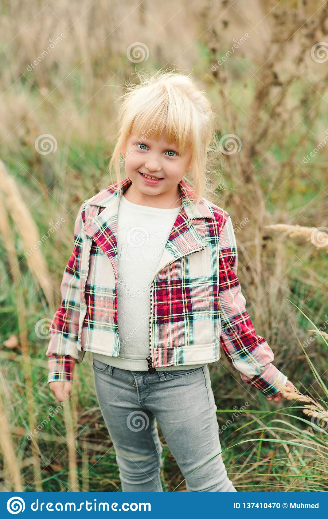 Cute little girl walking at countryside. Fashionable little girl with blue eyes and blondy hair. Kids fashion. Happy child at