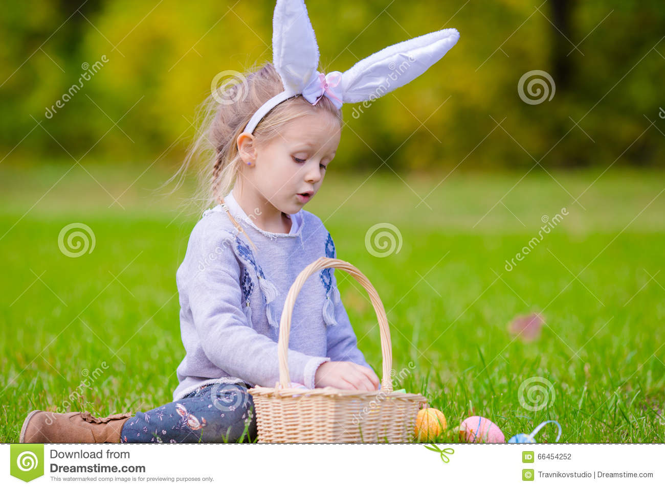 Cute Little Girl Wearing Bunny Ears Holding A Basket With