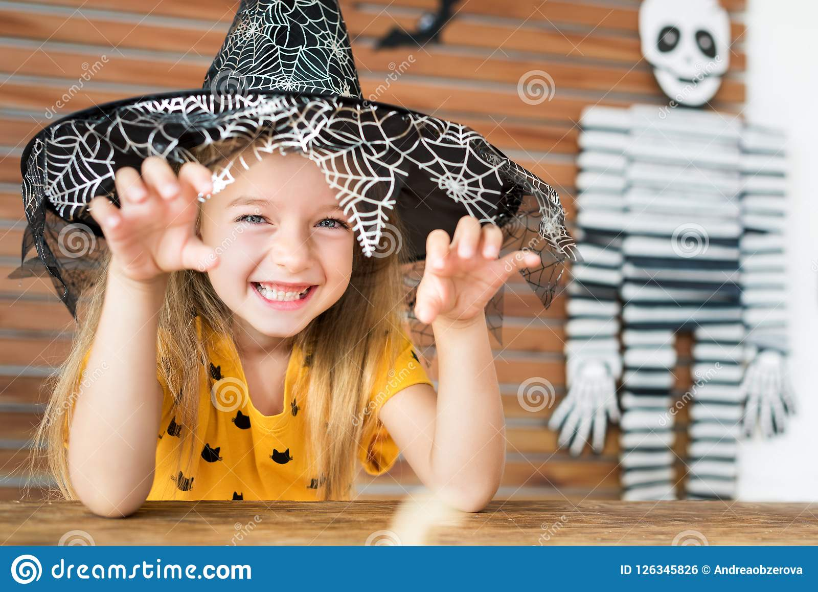 Cute little girl wearing witch hat sitting behind a table in Halloween theme decorated living room, making scary face.