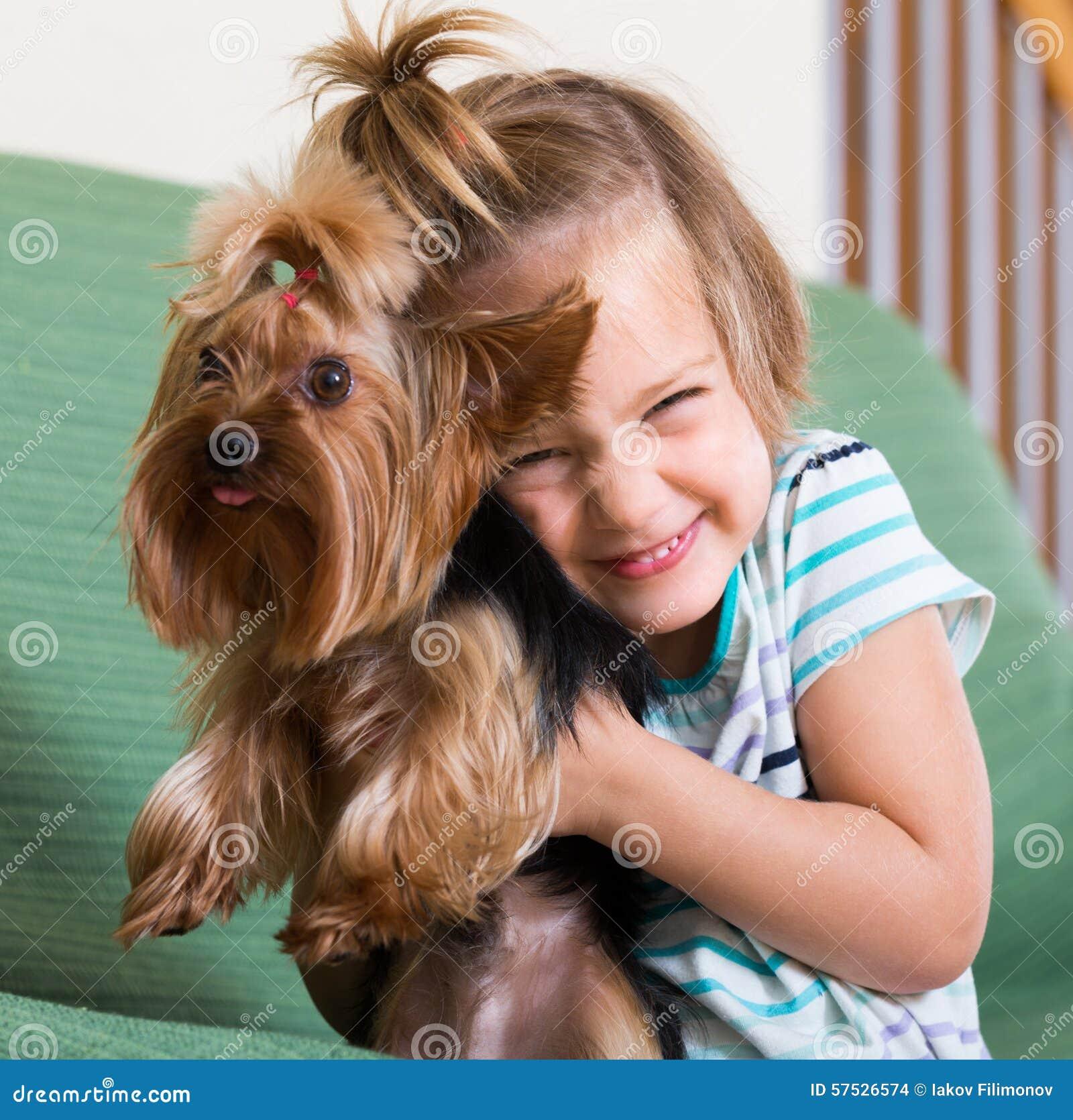 Free Hug Sofa Female Child Playing With Yorkie Royalty Free Stock Image