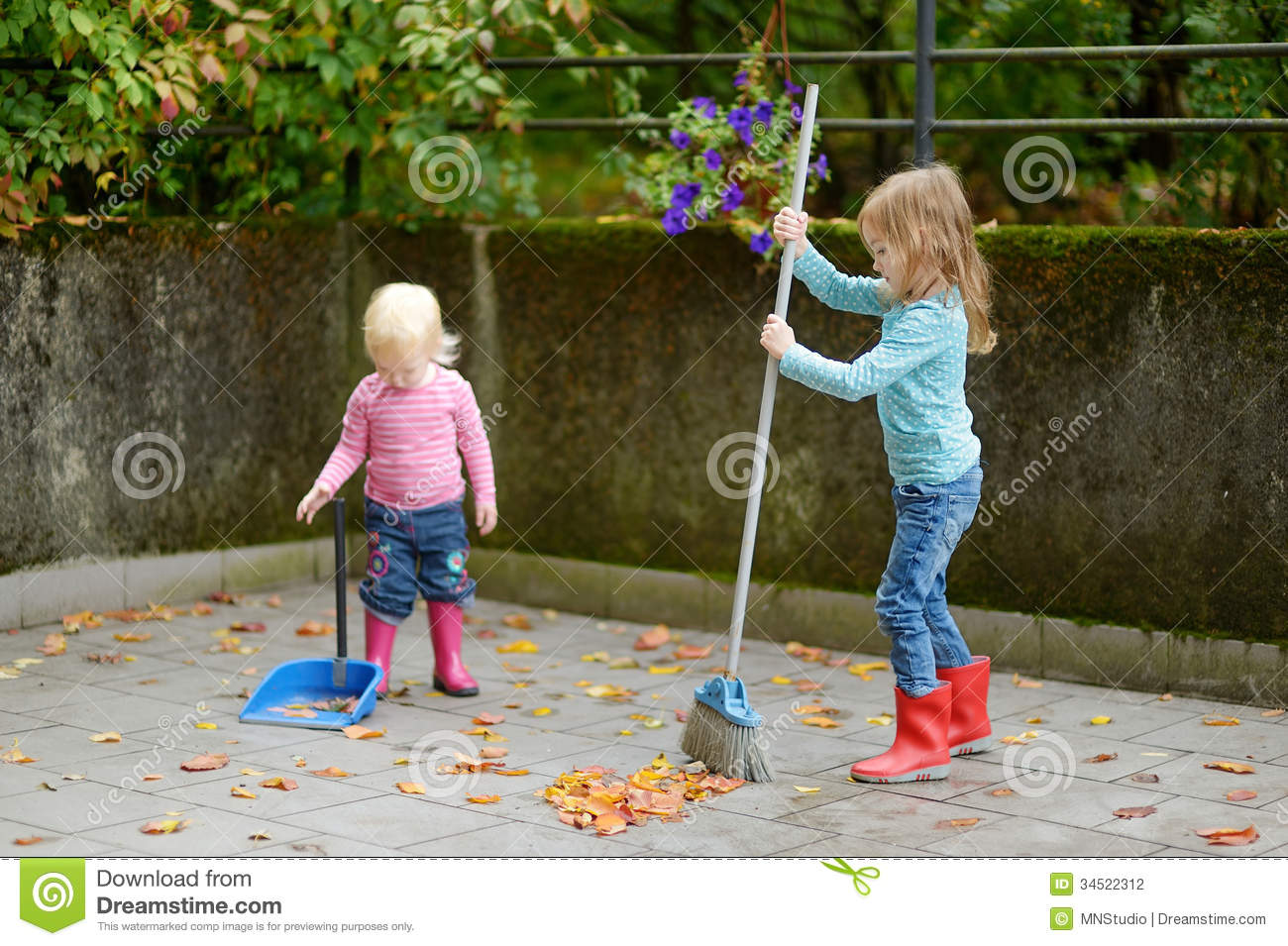 Cute Little Girls Sweeping Dry Leaves On Autumn Stock