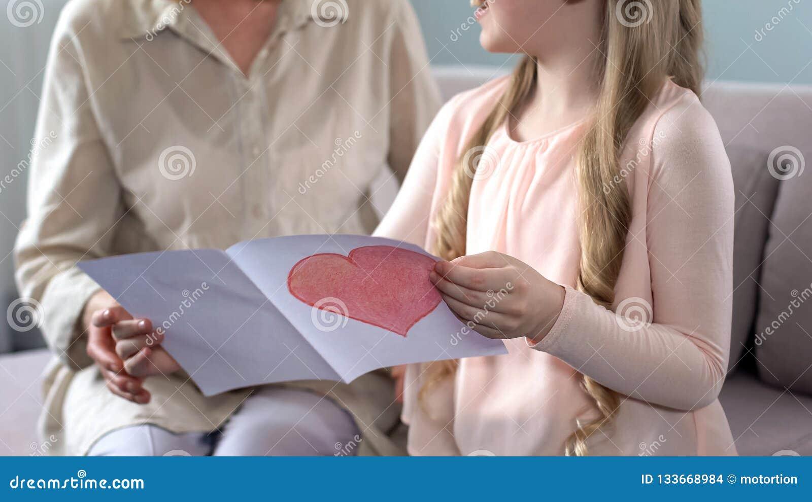 Cute little granddaughter presenting handmade greeting card to grandma, birthday