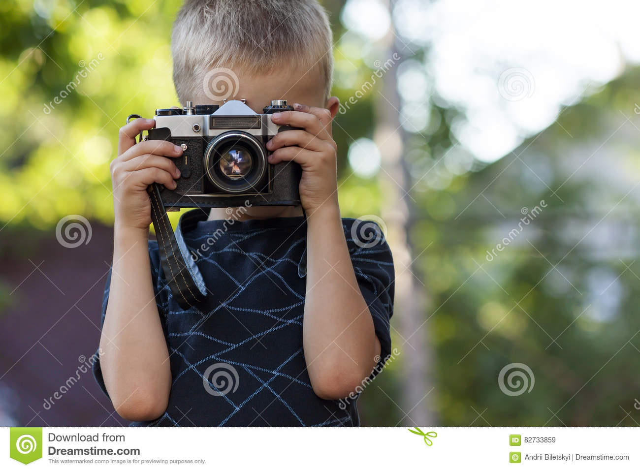 Cute little happy boy with vintage photo camera outdoors.