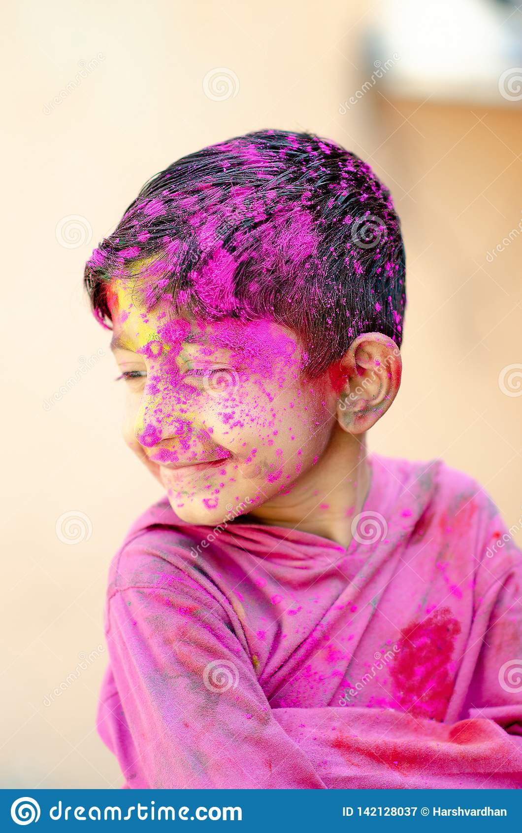 Cute Little Indian boy child with coloured face paint poweder color thrown at his face during holi indian festival looking at