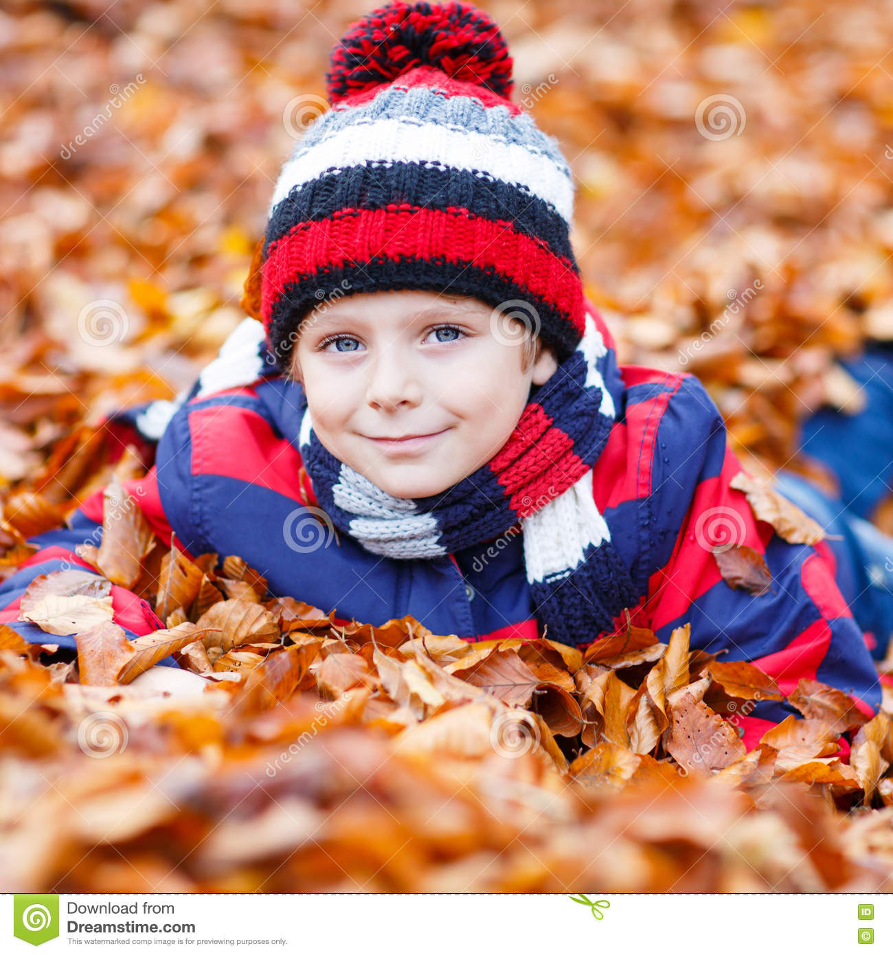 6096f68d48c Funny child having fun in fall forest or park on cold day. With hat and  scarf