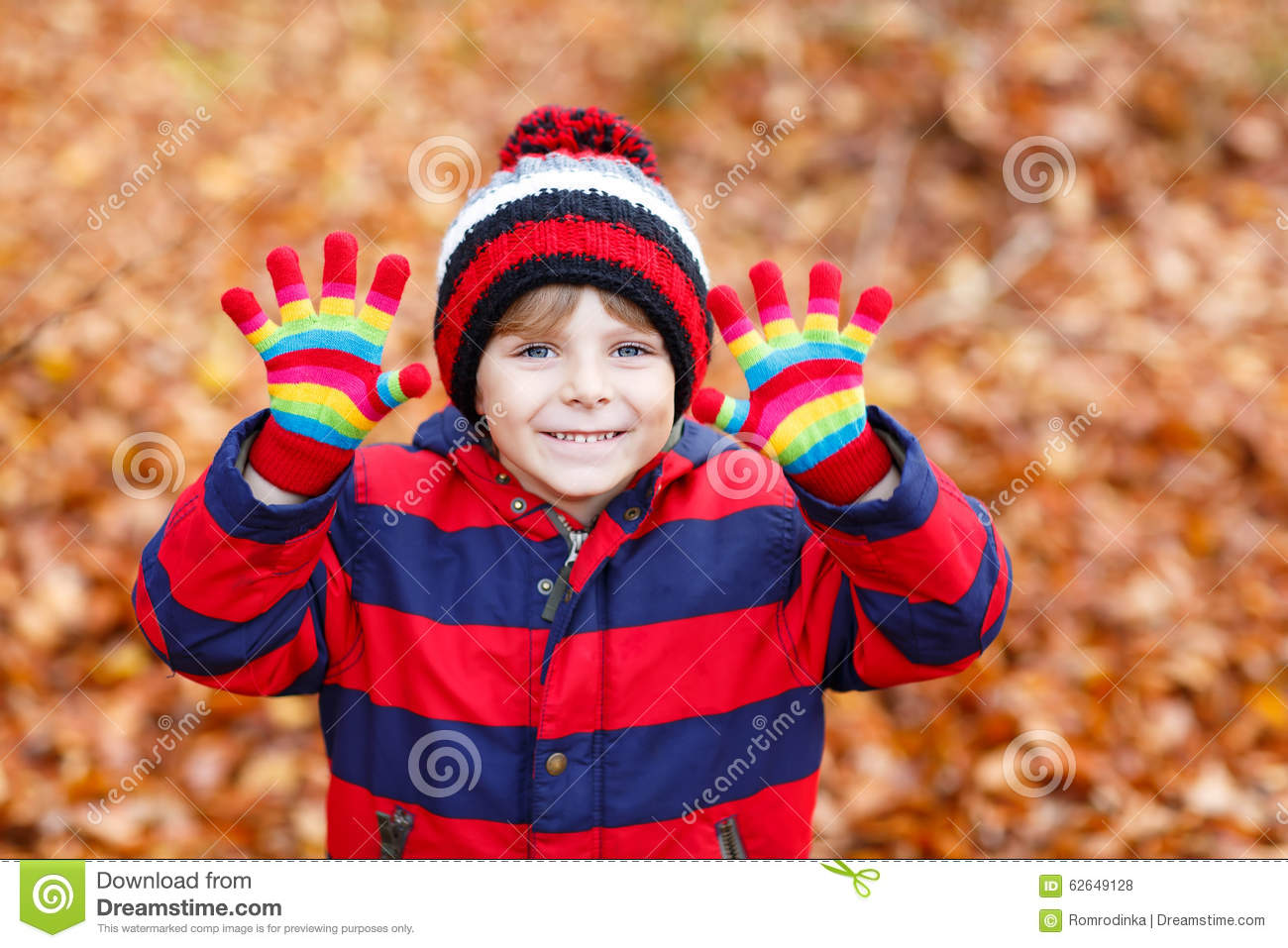 4dfcf0ad001 Funny child having fun in fall forest or park on cold day. With hat and  gloves