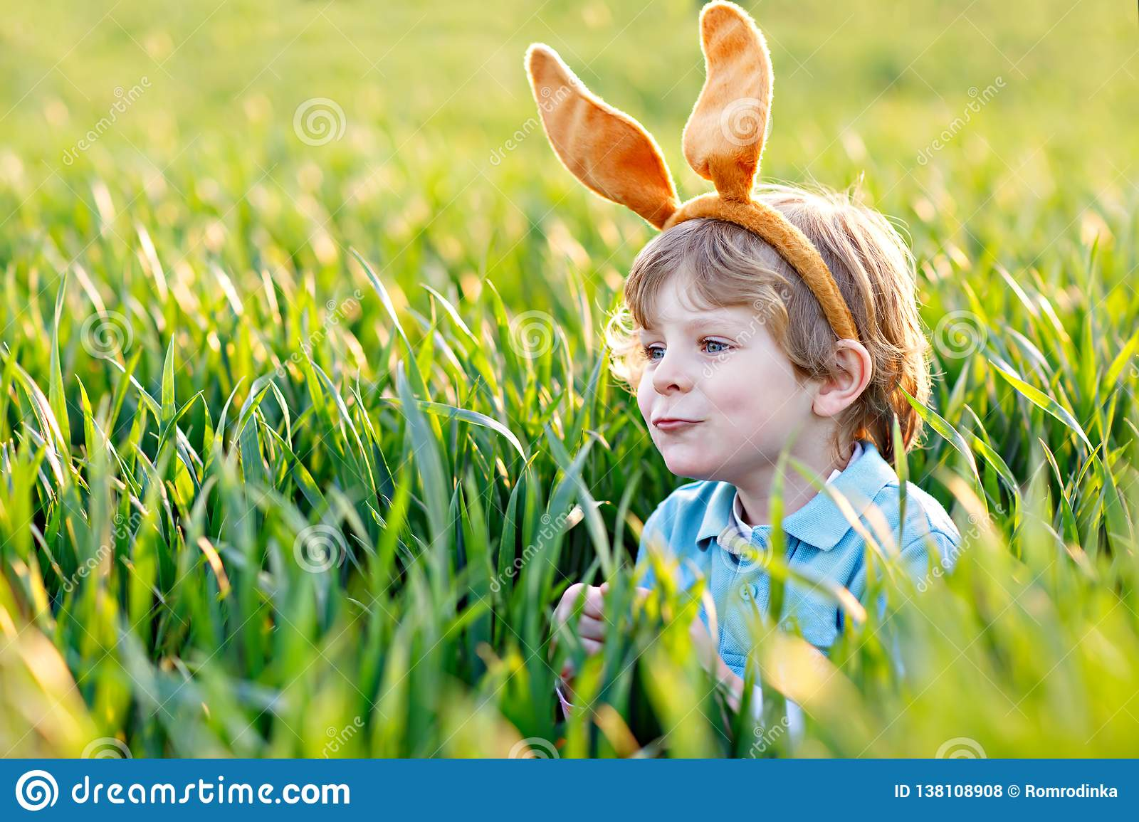 Cute little kid boy with bunny ears having fun with traditional Easter eggs hunt on warm sunny day, outdoors