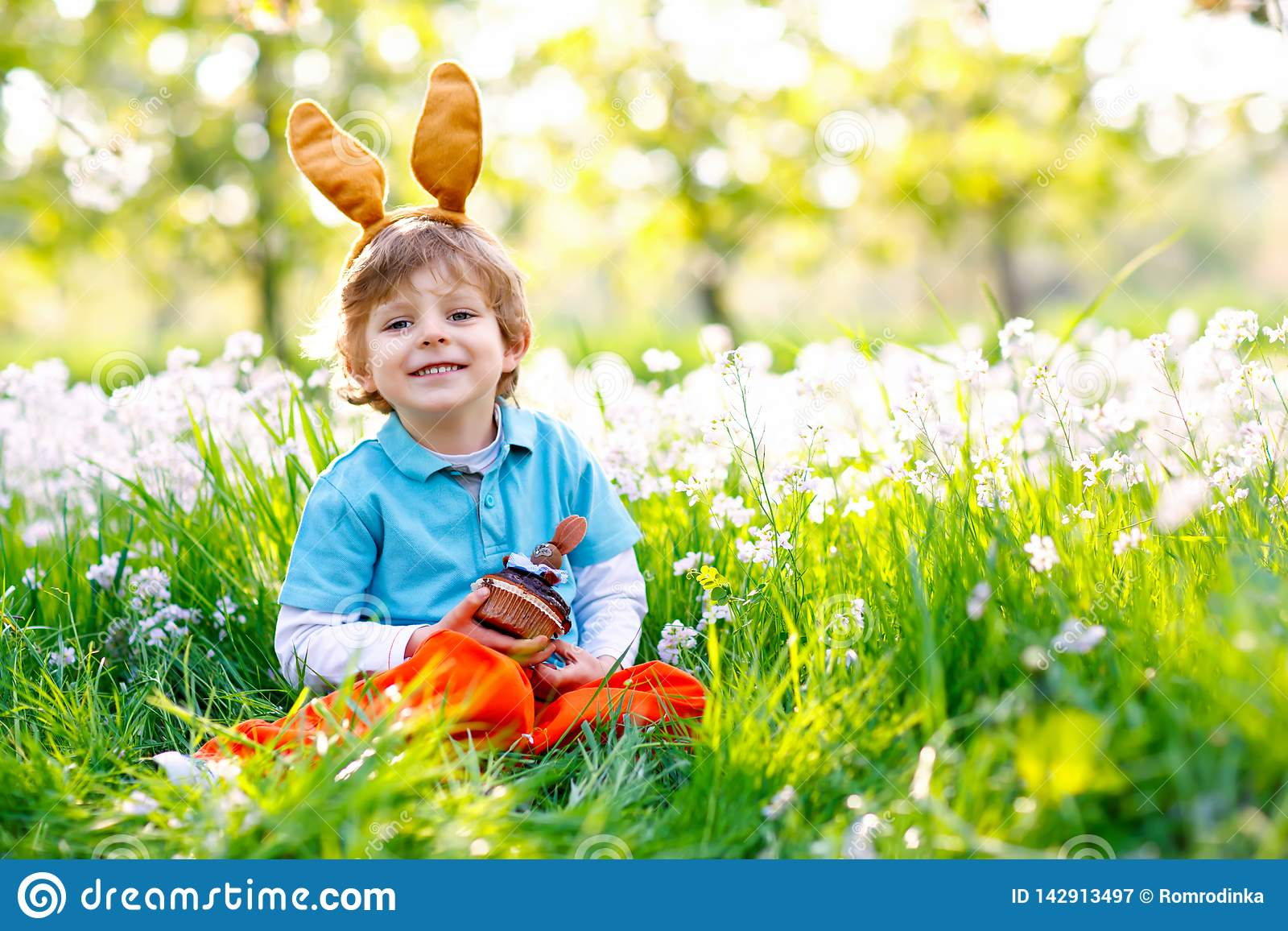 Cute little kid boy with Easter bunny ears celebrating traditional feast. Happy child eating chocolate cake of muffin on