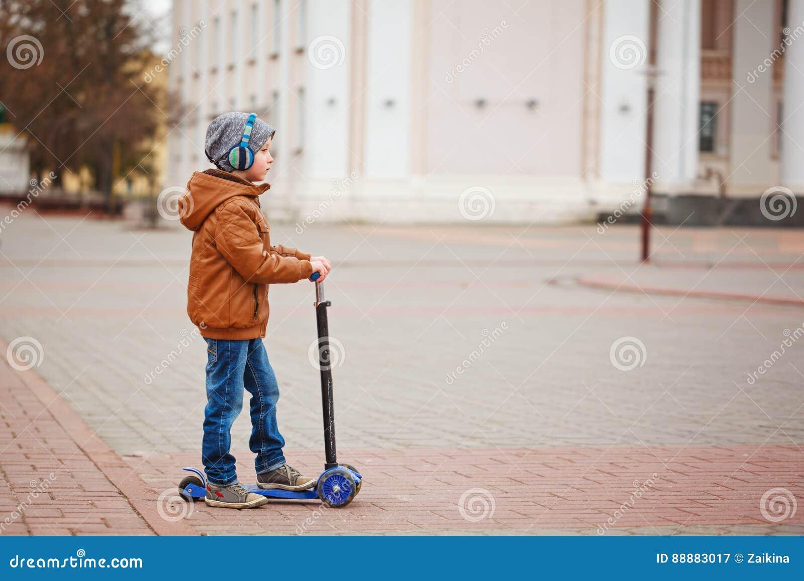 Cute Little Kid Boy Riding On Scooter Children Actitvities Outdoor