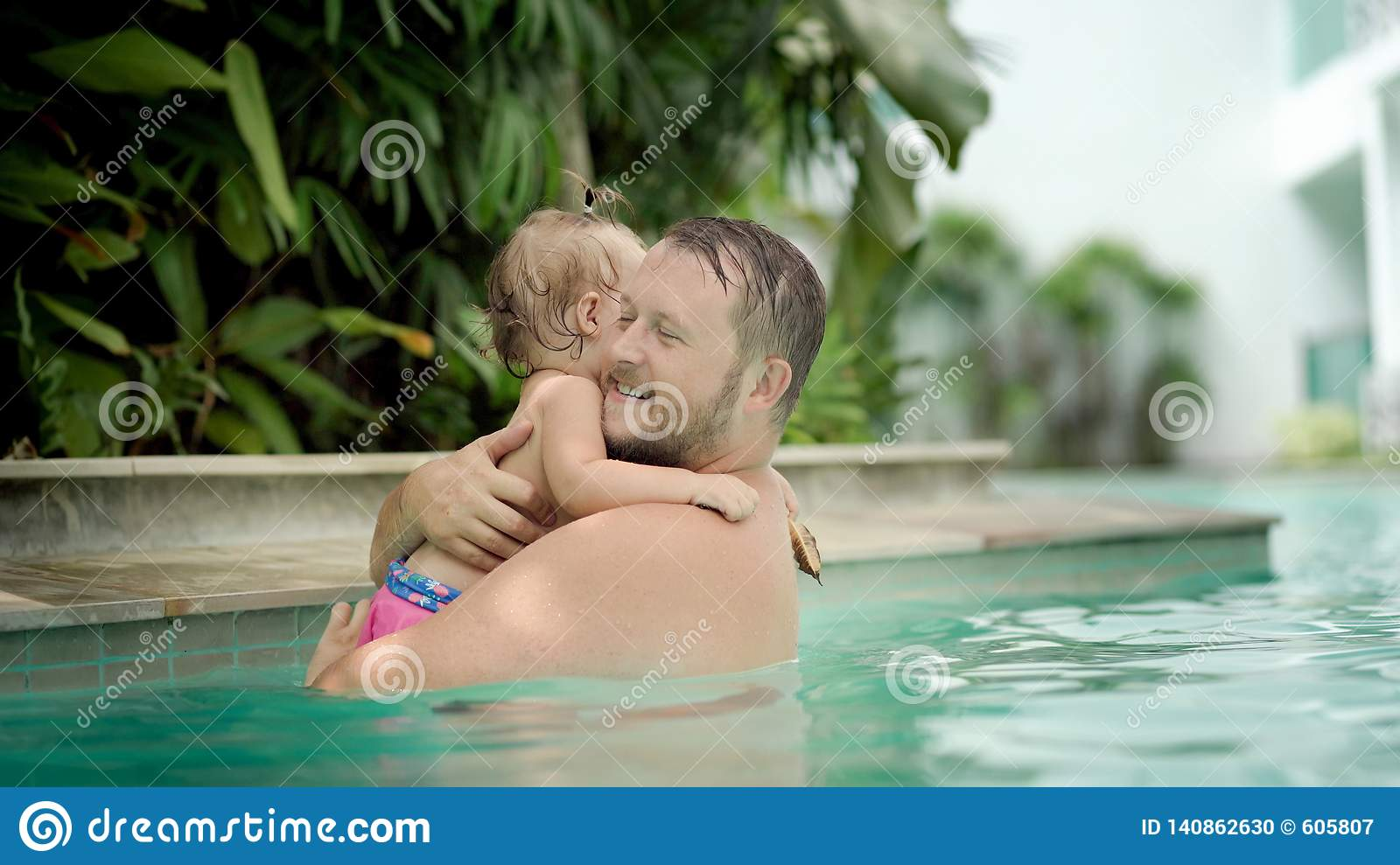 Cute little kid and his father having a swimming lesson in the pool. Father holds daughter in his arms and hugs.