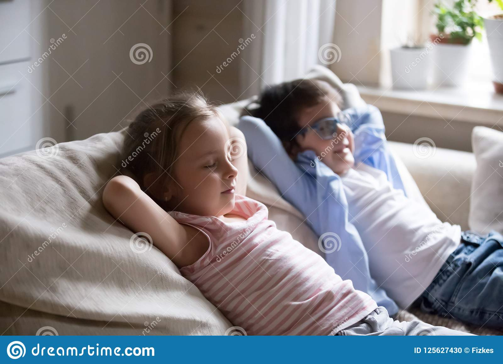 Cute boy and girl lying on cozy sofa relaxing