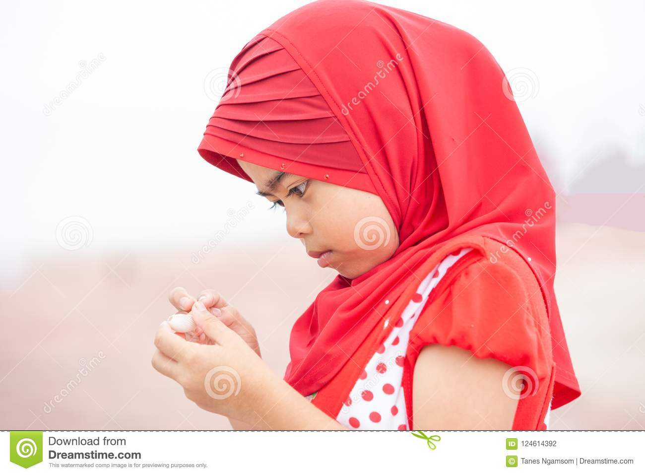 cute little muslim girl in traditional clothing red hijab or ni