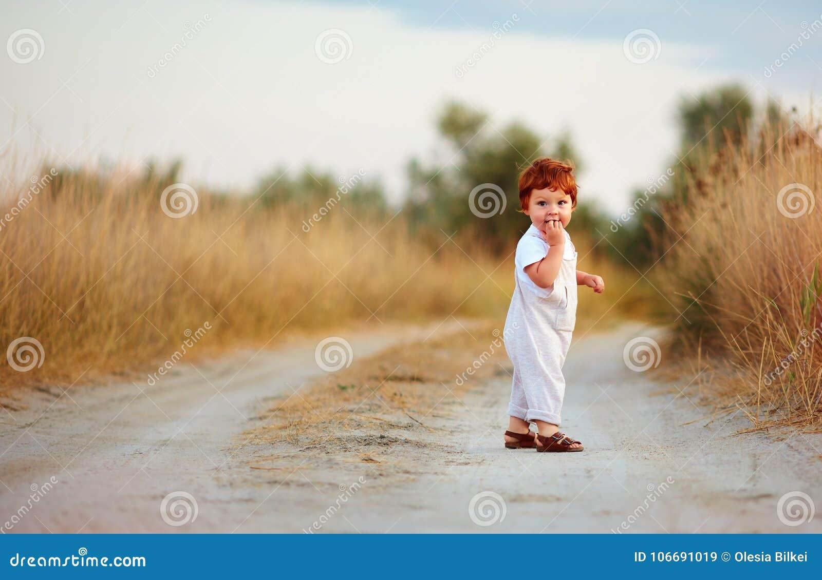 Cute little redhead baby boy walking on rural path at summer day