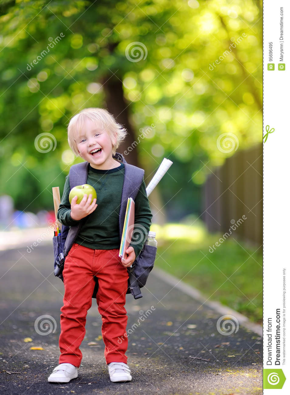 Cute little schoolboy with his backpack and apple. Back to school concept.