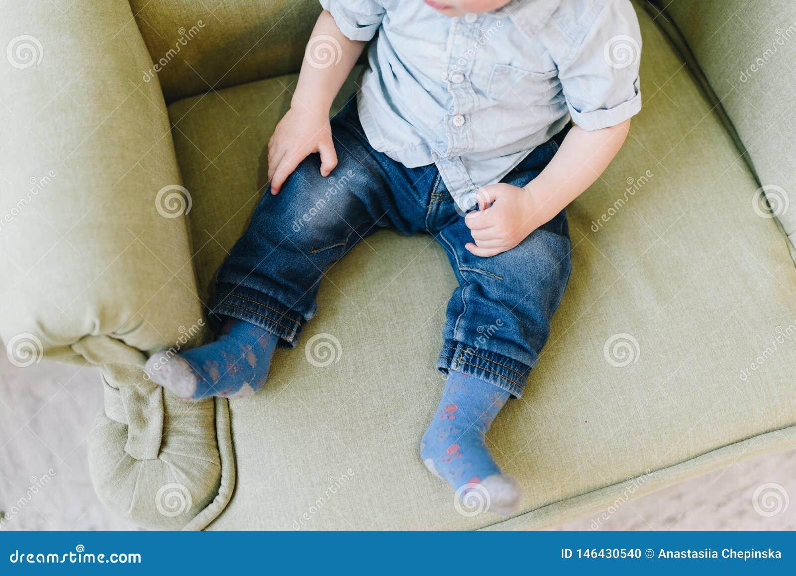 Cute little toddler boy sitting in armchair