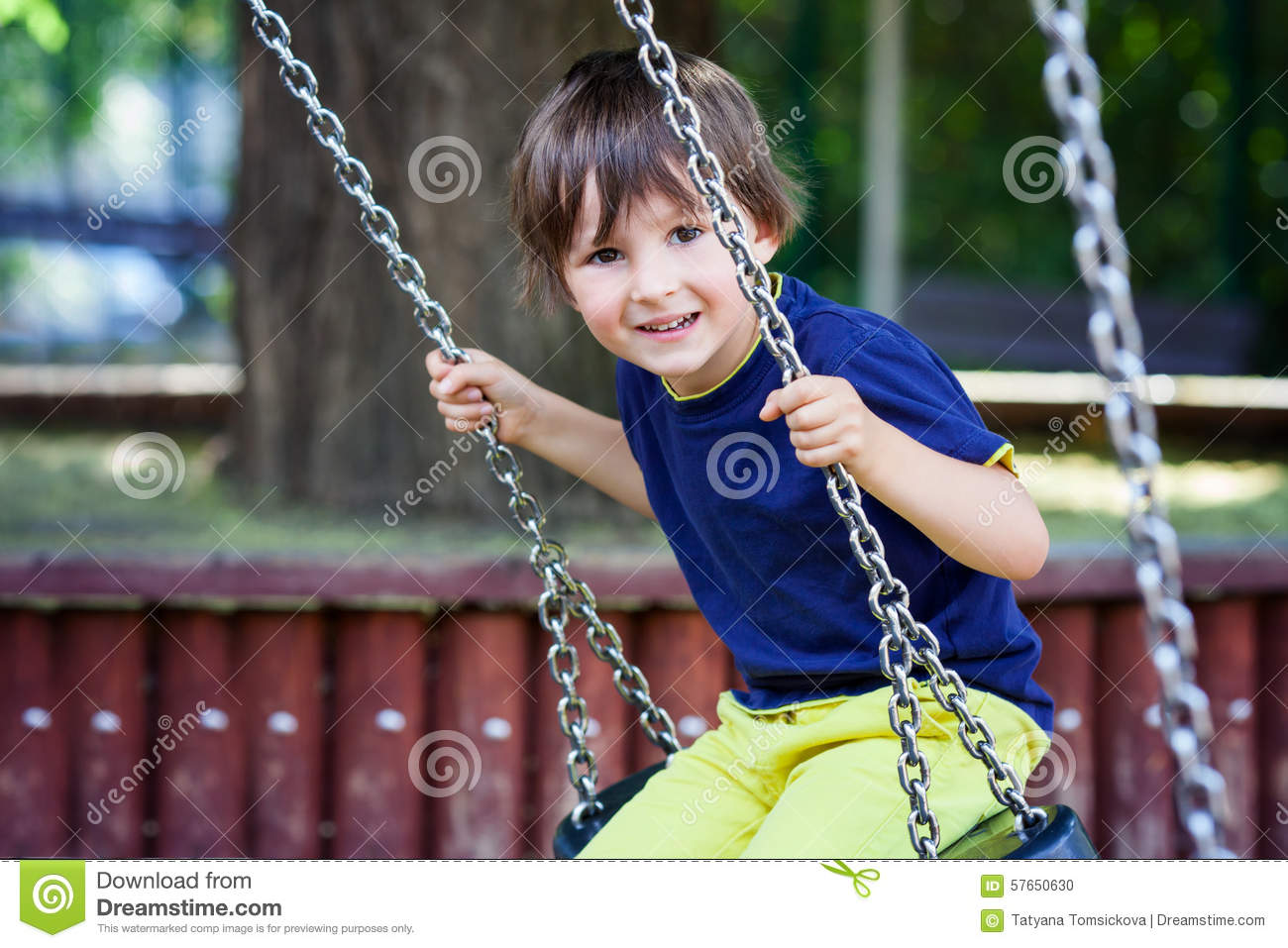 Cute little toddler boy, swinging in the park, summertime