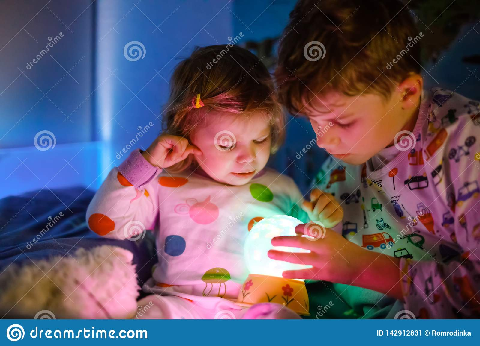 Cute little toddler girl and kid boy playing with colorful night light lamp before going to bed. Sleepy tired baby