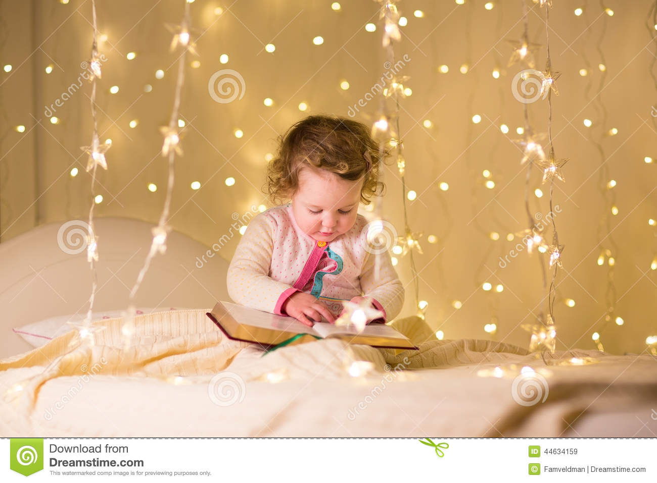 Cute little toddler girl reading book in dark room with Christmas lights