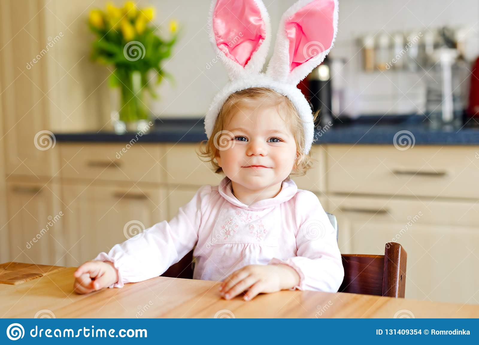 Cute little toddler girl wearing Easter bunny ears playing with colored pastel eggs. Happy baby child unpacking gifts