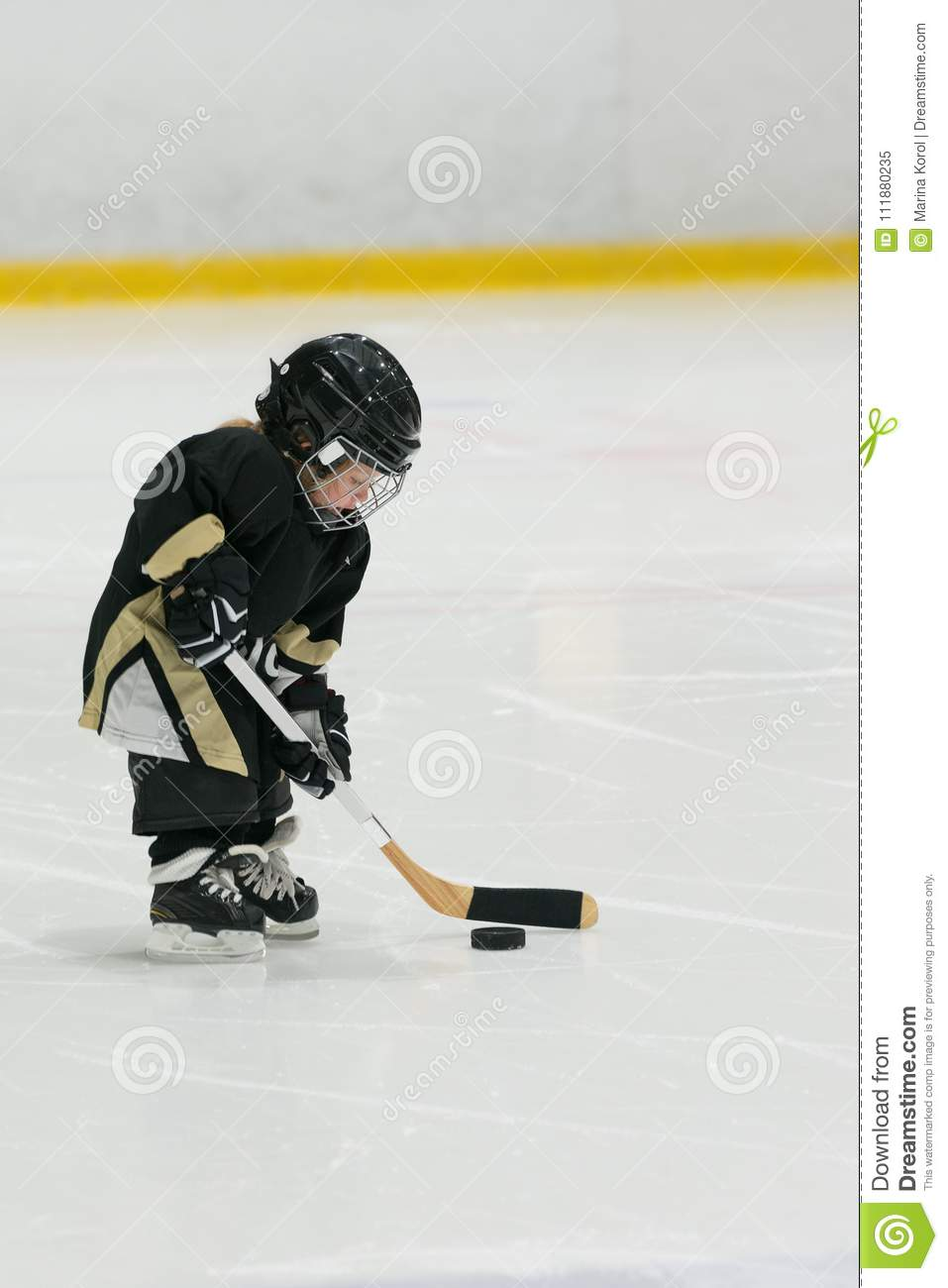 Cute little toddler plays hockey on ice with full equipment