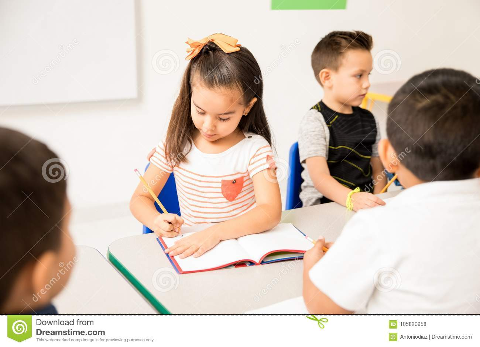 Hispanic preschool girl working in class