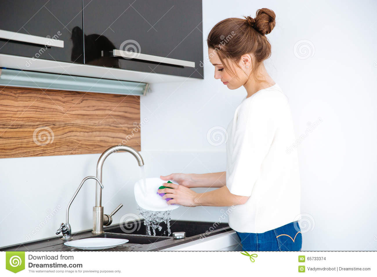 Cute lovely woman standing and washing dishes