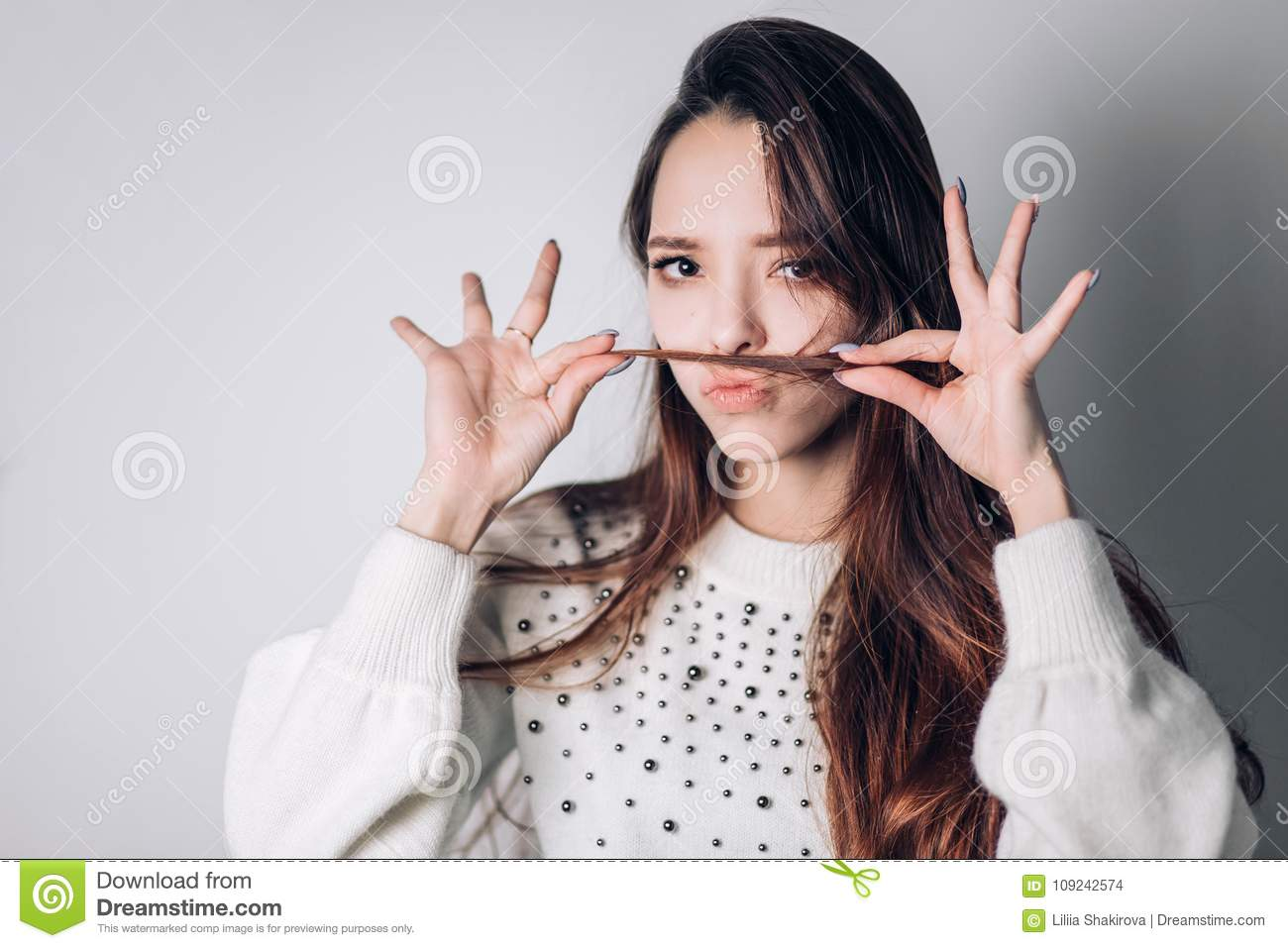 Cute lovely young woman making moustache with her hair over white background. The girl makes a face that shows emotions,